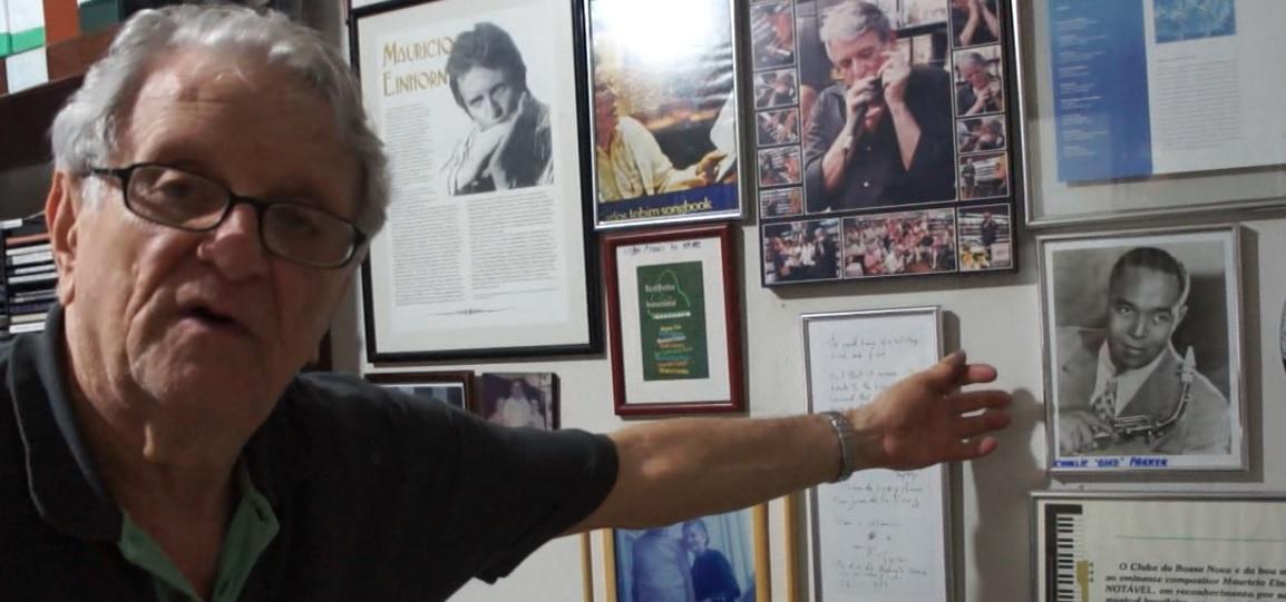 Em casa: Maurício Einhorn aponta para retrato de Charlie Parker Foto: Frame de vídeo/coisasdamusica